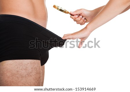 Close-up of woman's hand holding magnifying glass looking into man's underwear - stock photo