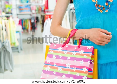 Close-up of woman?s hand holding paper bag while going shopping in the mall - stock photo