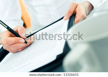 Close-up of woman's hand holding pen over document during work