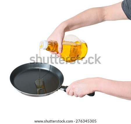 Close-up of woman's hand poured from a bottle of vegetable oil in a frying pan isolated on white. - stock photo