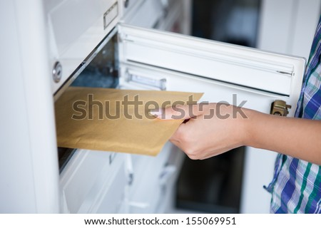 Close-up of woman's hand pulling envelop from mailbox - stock photo
