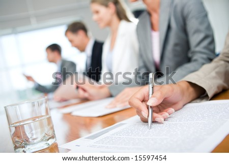 Close-up of womanâ??s hand with pen over document on background of business group - stock photo