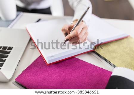Close up of woman's hand writing notes in notebook.  - stock photo