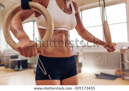 Close up of woman's hands holding gymnastic rings. Fit female working out with rings at gym. - stock photo