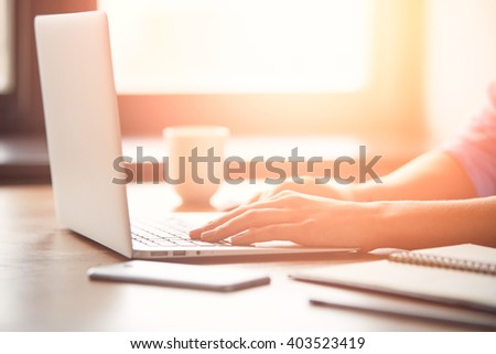 Close-up of woman's hands keyboarding on the computer. Cropped view of a young freelance female wearing blue shirt working on her laptop while sitting in coffee shop  - stock photo