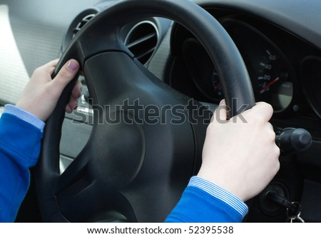 Close-up of woman's hands on the wheel in her car - stock photo
