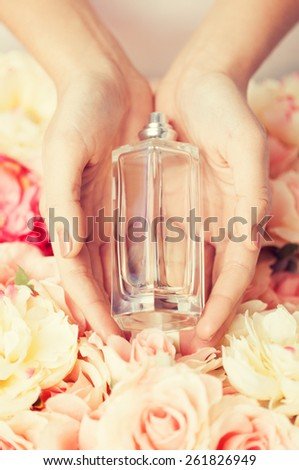 close up of woman's hands showing perfume - stock photo