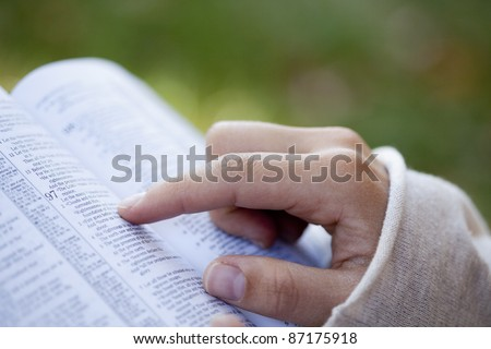 Close-up of woman's hands while reading the Bible outside. - stock photo