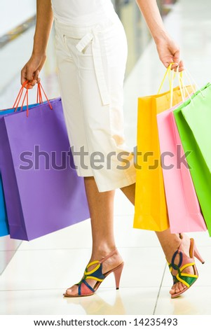 Close-up of womanâ??s legs with paper bags in her hands - stock photo