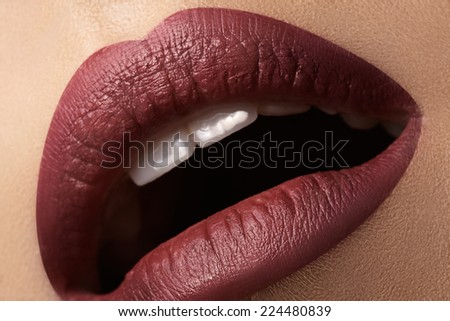 Close-up of woman's lips with bright fashion dark red makeup. Macro cherry lips make-up. Evening sexy visage  - stock photo