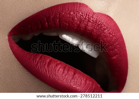 Close-up of woman's lips with bright fashion red marsala makeup. Macro deep wine color lipstick make-up. Sexy kiss