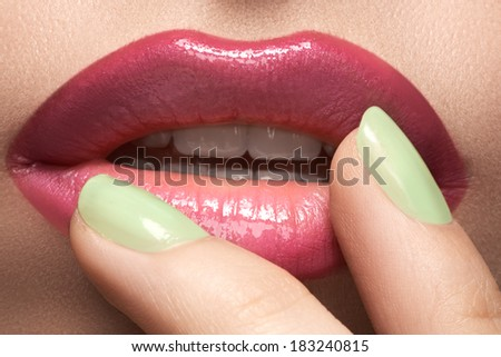 Close-up of woman's lips with fashion hot pink lipstick makeup. Beauty macro sexy make-up with bright mint green color on nails.  - stock photo