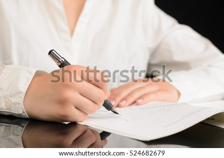 Close up of woman signing a document or a contract