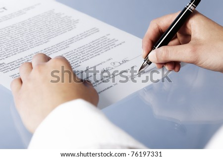 Close up of woman signing a legal document or contract, blank background. - stock photo