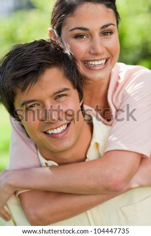 Close-up of woman smiling while looking in front of her as she is being carried bey her friend in a park - stock photo