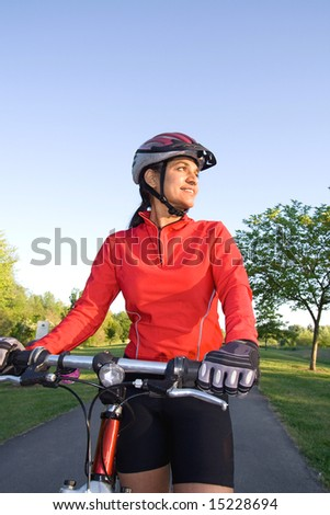 Close-up of woman standing next to bicycle and smiling in the park. Wearing sports gear and helmet. Vertically framed shot. - stock photo