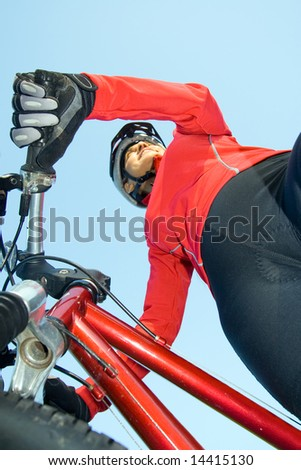 Close-up of woman standing next to bicycle smiling. Wearing sports gear and helmet. Vertically framed shot. - stock photo