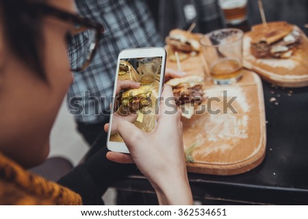 Close Up Of Woman Taking Picture Of  Delicious Burger Using Smart Phone - stock photo