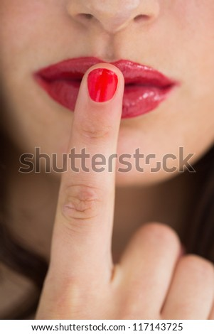Close-up of woman touching her red lips with red nail