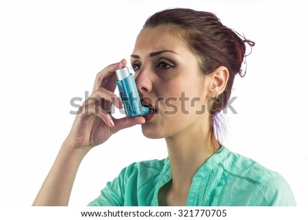 Close-up of woman using asthma inhaler against white background - stock photo