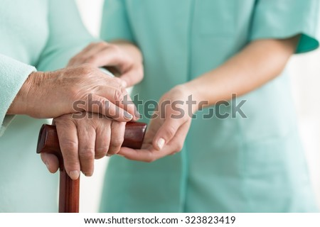 Close-up of woman using cane assisted by physiotherapist - stock photo