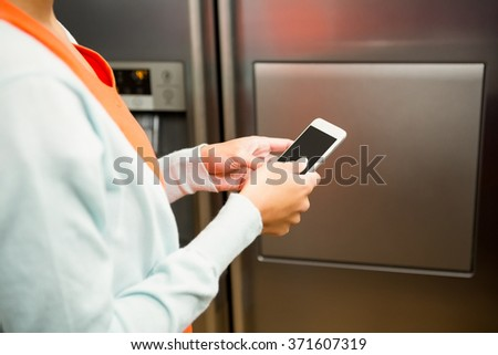 Close up of woman using smartphone near the refrigerator in the kitchen - stock photo