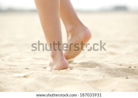 Close up of woman walking barefoot on sand - stock photo