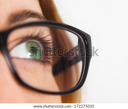 Close up of woman wearing black eye glasses looking up - stock photo