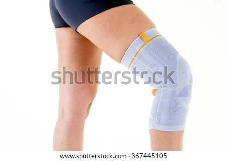 Close Up of Woman Wearing Flexible Elastic Supportive Orthopedic Brace on Bent Knee in Studio with White Background