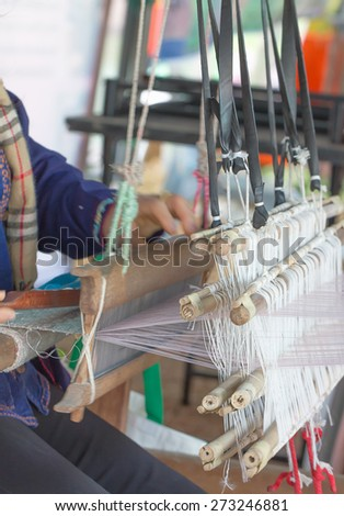Close up of  woman weaving white pattern on loom in Chiang Mai Thailand