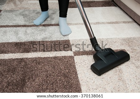 Close up of woman with legs vacuum cleaner cleaning carpet at home