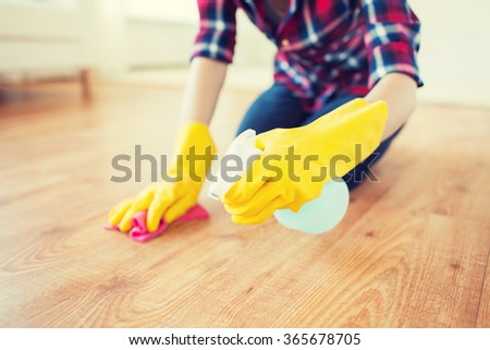 close up of woman with rag cleaning floor at home - stock photo