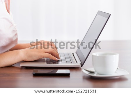Close-up Of Woman Working On Computer In Office - stock photo