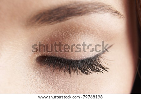 close up of womans brown eye lid with false eye lashes - stock photo