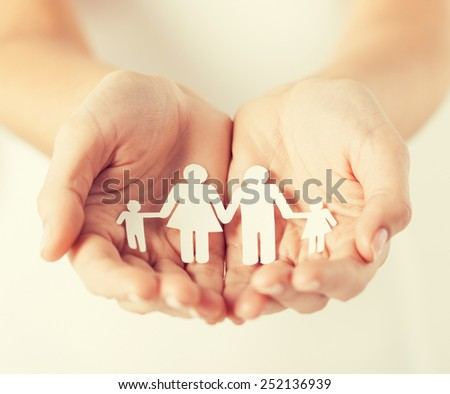 close up of womans cupped hands showing paper man family - stock photo