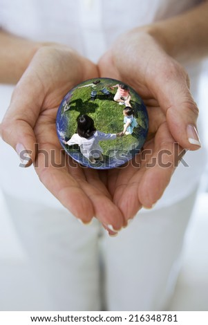 Close up of womanxE4xF3xBBs hands cupping crystal ball globe with children
