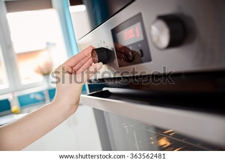 Close up of women hand setting cooking mode or temperature on oven - stock photo