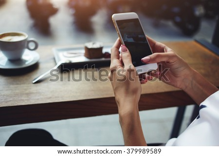 Close up of women's hands holding cell telephone with blank copy space scree for your advertising text message or promotional content, hipster girl watching video on mobile phone during coffee break  - stock photo