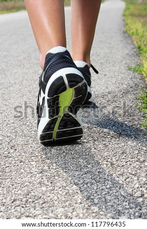 Close-up of Women's running shoes on a paved trail. - stock photo