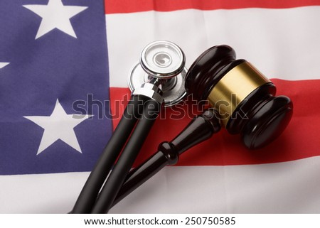 Close-up Of Wooden Brown Gavel And Stethoscope On Usa Flag - stock photo