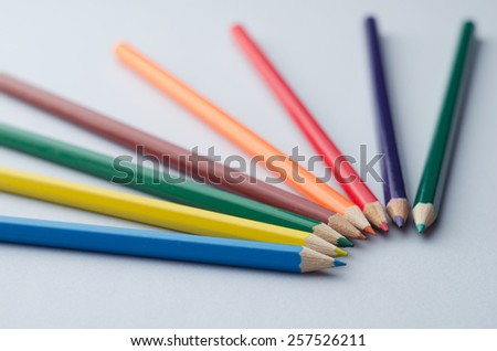 Close up of wooden colored crayons in a circle over blue background, shallow depth of field - stock photo