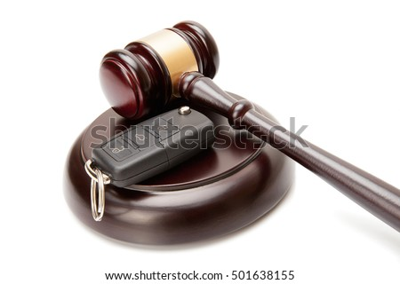 Close up of wooden judge gavel and car keys over soundboard on white background
