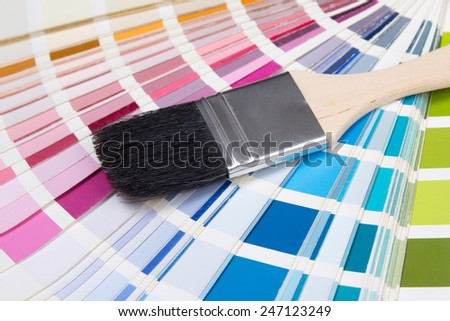 close up of wooden painter's brush over colorful palette - stock photo