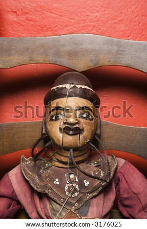 Close up of wooden puppet sitting on chair. - stock photo