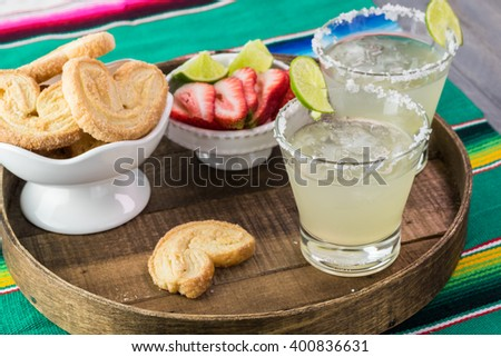 Close up of wooden tray with glasses of margarita cocktail garnished with salt rim and lime on fiesta decorated table. - stock photo