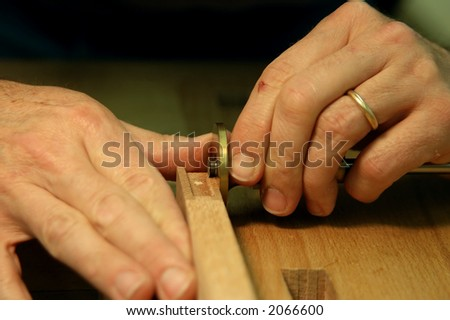 Close Up of woodworkers hands measuring for a hinge
