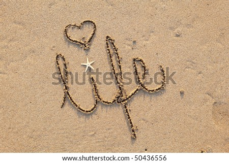 close up of word 'life' written in sand at beach