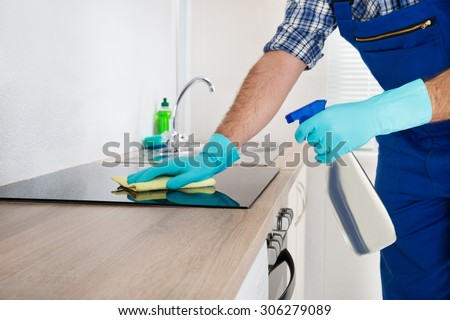 Close-up Of Worker Cleaning Electric Hob At The Countertop With Cloth - stock photo