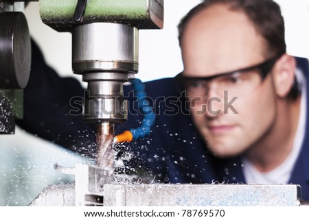 Close up of worker with safety glasses at milling machine in workshop. - stock photo