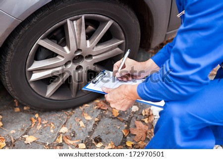 Close-up Of Worker Writing On Clipboard Sitting Near Car - stock photo